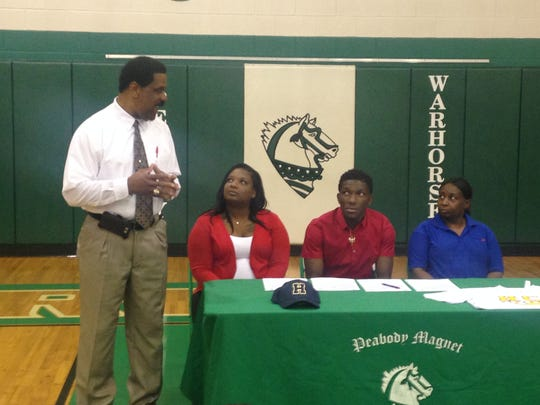 Peabody coach Charles Smith (left) talks as Danmons O'Connor (second from right) is set to sign with Highland Community College.