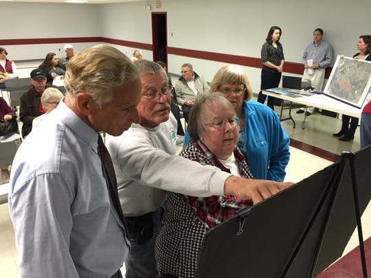 Ronald De Clement, Bob Mayne, Maron Atkins and Deanna Mayne look over OneEnergy Renewable's plans to build a large solar farm Thursday, May 5, at a hearing at the Somerset County Civic Center.