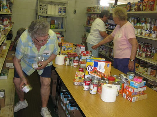 Harriette Dunckel, left, and a group of volunteers sort food to be stocked on the shelves at the Williamston Community Food Bank in June 2009.