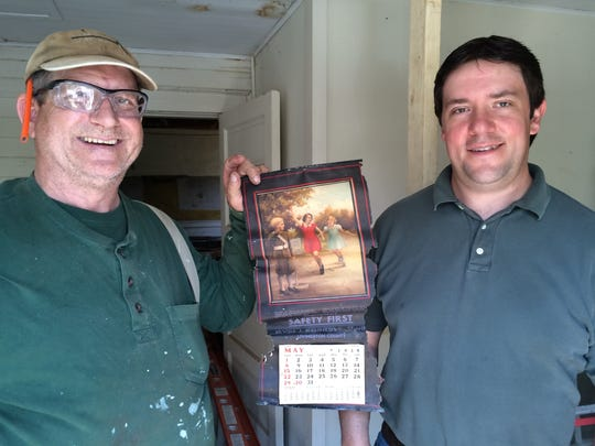 Archaeologist Tim Bennett (right) and historical restoration specialist contractor Randy Klepinger (left) show off a 1938 calendar that had slipped behind a slate blackboard in the 1849 Hicks one-room schoolhouse. Bennett will move the schoolhouse building to his family's historic farm where he does archaeological digs.