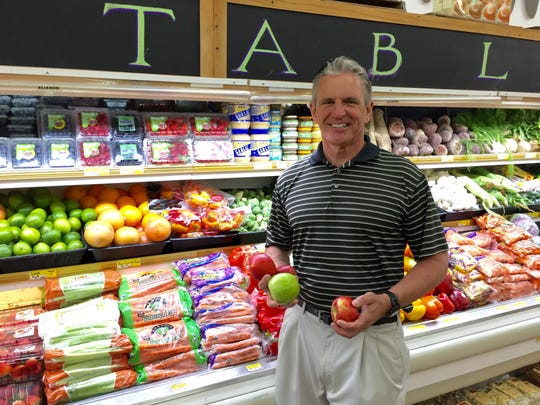 David Apple, owner of Apple Market, poses inside the store.