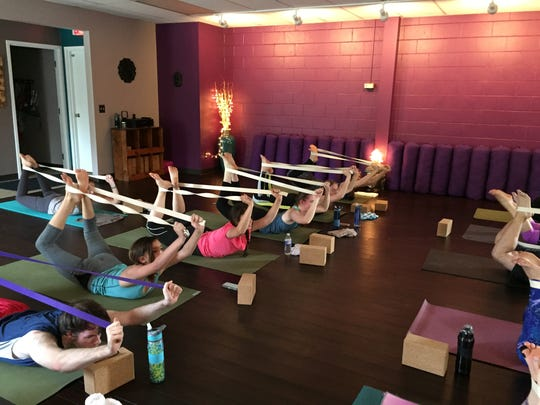 Mosinee High School students use belts to stretch at Fearless Yoga in Wausau on Monday, May 9, 2016.