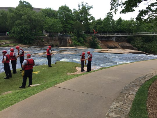 A swift water rescue class with the Greenville Fire Department practices rescues in the Reedy River in downtown Falls Park on May 10, 2016.