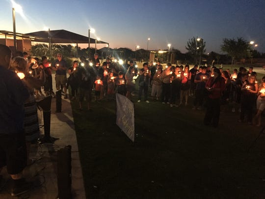 Roughly 50 friends and family members light candles