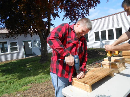 "Aumsville Police Chief Richard Schmitz works on the community ""Panther Garden"" at Aumsville Elementary School."