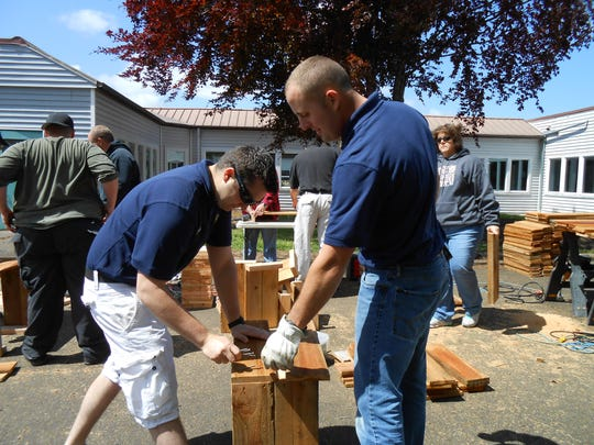 "Reserve Officers Chris Chabot and Ken Buchheit work on the Aumsville community ""Panther Garden."""