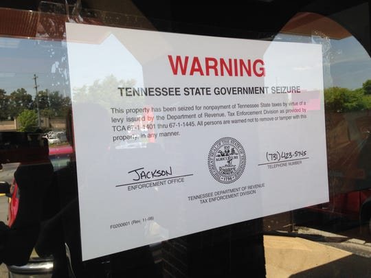 A sign at the front entrance at Dunkin' Donuts states the restaurant has been closed because of unpaid taxes.