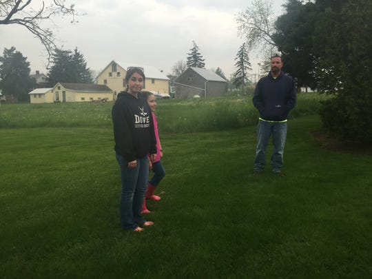 Homeowner Wayne Weaver, right, stands in his backyard with his daughters Kayla, left, and Katherine, center. The buildings in the background would likely be destroyed and the field would be paved over as part of a plant to convert the property into retail space.