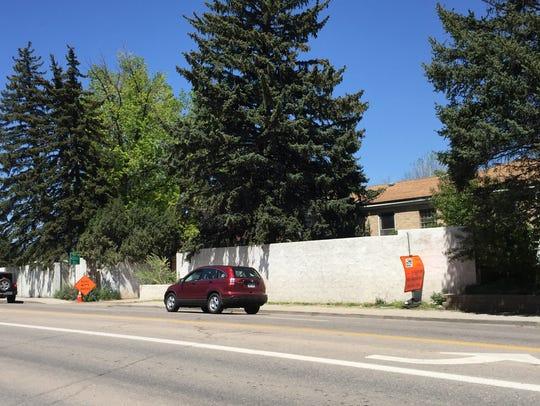 An 8-foot-tall retaining wall and several trees at