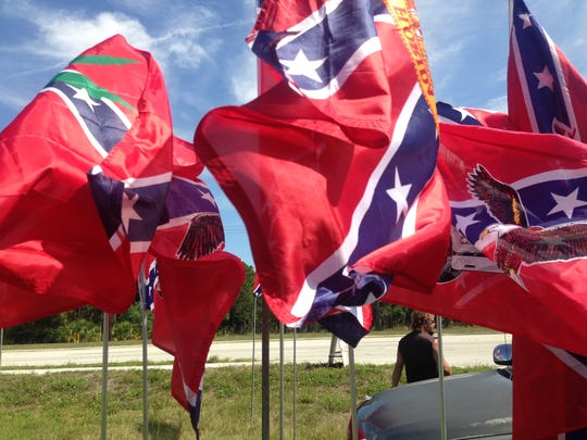 Ron Perry of R.C. Perry Flags, shows off his display of Rebel-influenced flags for sale at a small roadside stand along Bayshore Drive on Sunday in North Fort Myers.