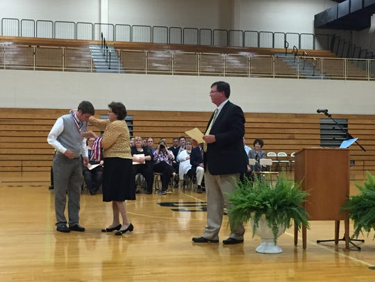 Austin Craig receives a Tennessee Scholars medal from