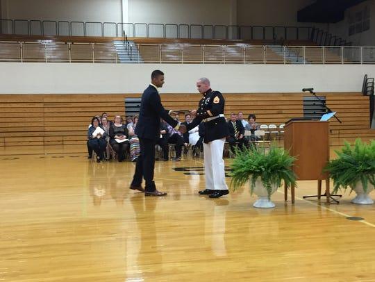 Brandon Ford, left, receives the U.S. Marines Scholastic