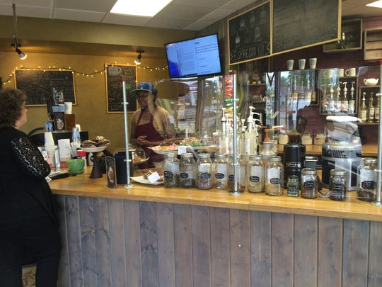 Bonnie Galloway serves a customer on Tuesday at Periwinkle's Coffee and Tea Shoppe