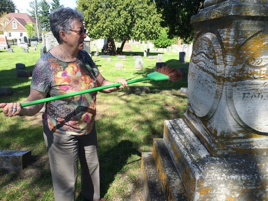 Barbara Krueger brushes off the grave of Robert Crouse in the Hartland Village Cemetery. She and her husband Dick will lead the Hartland Memorial Day Parade as this year's grand marshals.