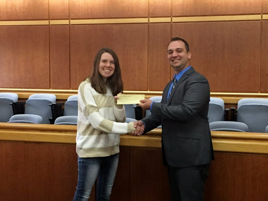 In this 2015 file photo Lance Leonhard, past president of the Marathon County Bar Association, hands a check to Peyton Medick. The Marathon County Bar Association raised more than $1,300 that year during its annual golf outing, and the funds were donated to Peyton's Promise, a local charity that helps fill food pantries.