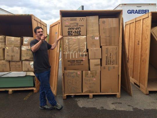 Thomas Hayward works to auction off storage crates