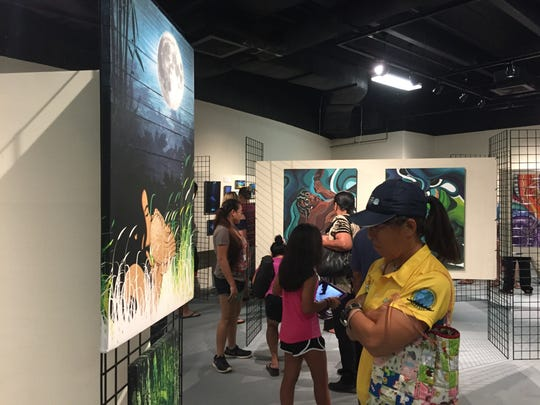 Residents look at art during the opening of the Festival
