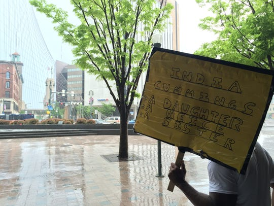 A protester holds a sign for India Cummings in the rain at the Liberty Pole in Rochester in 2016.