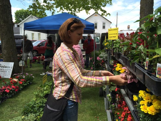 Jen Wachowski looks at marigolds and other plants on