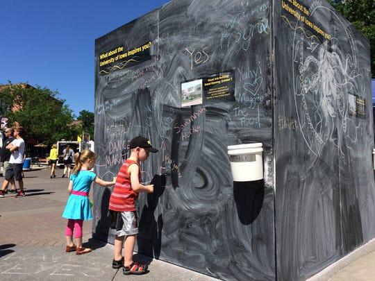 Zoe Sowers, 3, and Gowan Clark, 5, draw with chalk