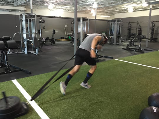 Coach TJ Christensen demonstrates how to pull a weighted sled during a workout.