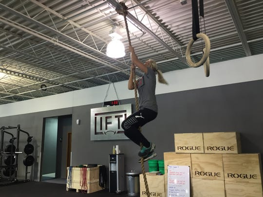 Manager Brook Haakenson demonstrates her talents in rope climbing at the Lift Athletics gym.