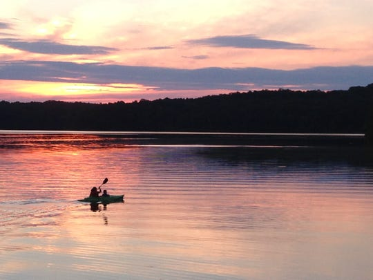 A woman rides out with her child in a kayak to enjoy the sunset in Sugar Bay at Land Between the Lakes on Memorial Day weekend 2016.
