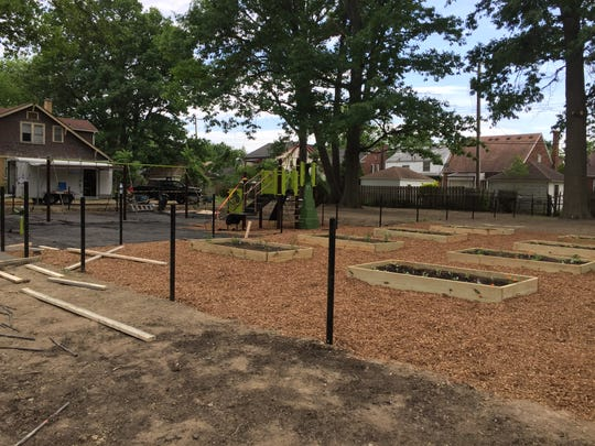 Volunteers helped put up new playground equipment, a community garden, sidewalks and fencing on a new neighborhood park built on formerly vacant lots on Detroit's east side on Tuesday, June 14, 2016.