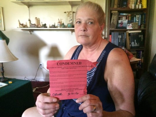 """Catherine Lynch shows the red """"condemned"""" tag attached to her mother's house in Delhi Township. The family was evicted from their own home after they couldn't pay their utility bills."""