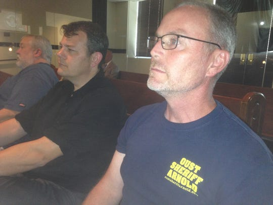 """Steve Lane, a member of Tennesseans Against Corruption, wears a T-shirt with the message """"Oust Sheriff Arnold"""" while at the Rutherford County Commission meeting. The commission voted 21-0 on a resolution asking Arnold to resign."""