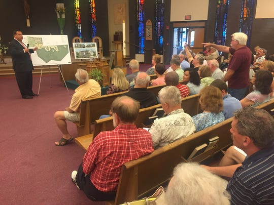 Attorney Larry Tarabicos explains the layout of the Our Lady of Grace housing development, off Chestnut Hill Road, near Newark, as residents look on at a public meeting earlier this year at Holy Family Church near Newark.