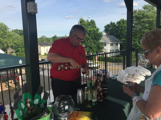 Conrad serves wine at the wine tasting event at Athletic Park.