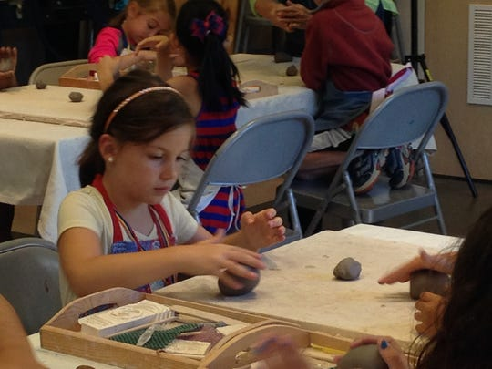 Children are shown how to mold blocks of clay into