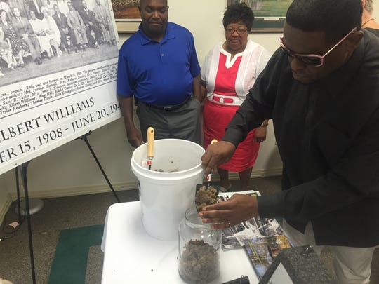 Gerald Tyus shovels soil from the bank of the Hatchie River to commemorate the death of Elbert Williams.