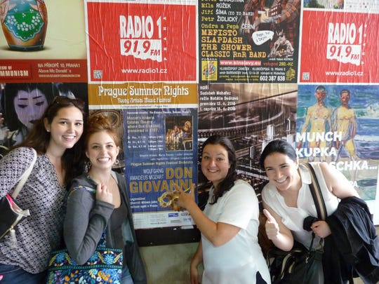"""Mozart's """"Don Giovanni"""" cast-mates stand by a poster"""