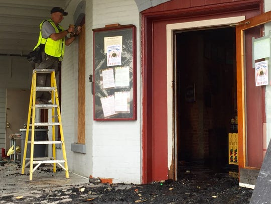 Walt Holden begins boarding up the windows of the burned-out