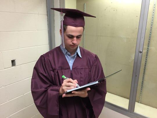 New Paltz High School senior Adam Joyner, 17, signs