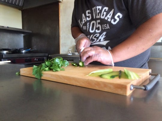 Newchee Lor prepares jalapenos to top off his banh mi sandwhich.