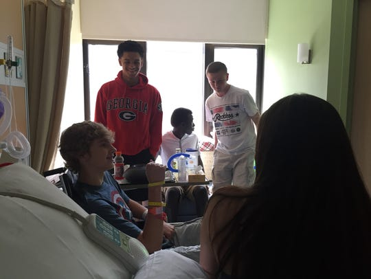 Danny Fleigle is visited in his hospital room by friends