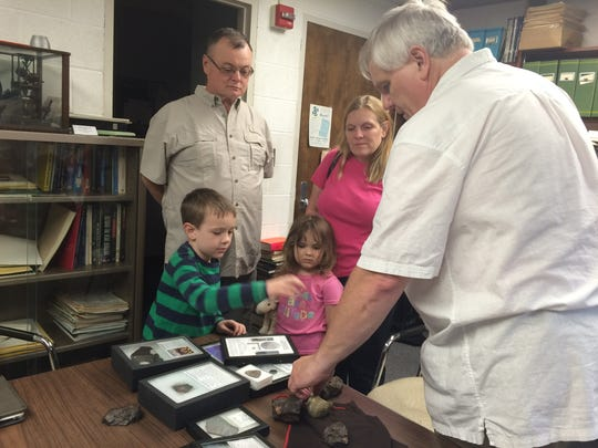 Craig Whitford, right, the meteorite collection coordinator at Abrams Planetarium at Michigan State University, shows meteorites to Daniel and Kathryn Seip and their children Tommy, 6, and Mary, 4.