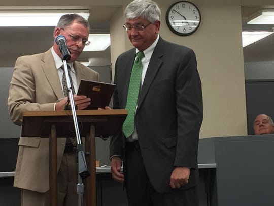 Attorney Ben Politz reads a plaque for Ron Looney during