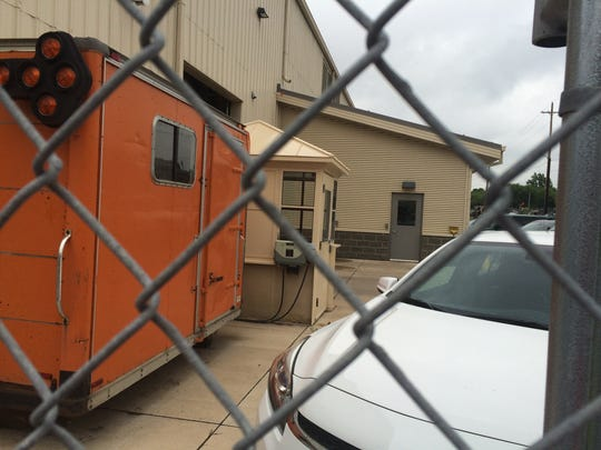 The small booth, to the right of the orange trailer, behind the city's Facilities Services building was being painted when a gust carried paint across the city employees' parking lot.