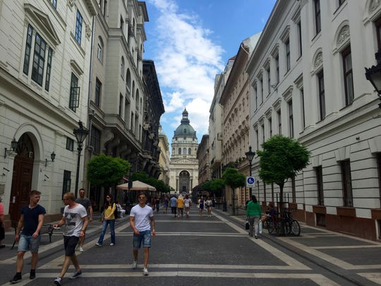 People walk down a street in downtown Budapest, June