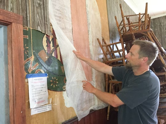 Aaron Worthley uncovers a wall painting left by the Modern Woodmen of America, who built what is now Huntington's old Town Hall in 1903.
