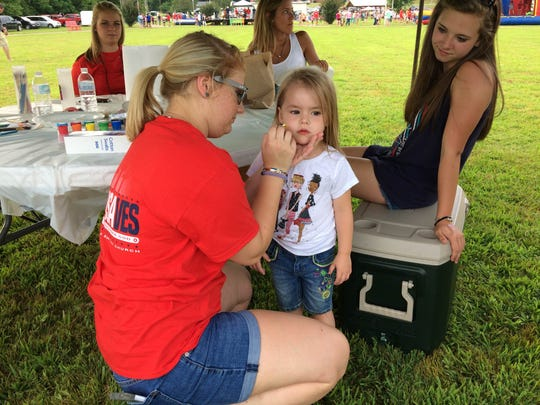 Emory Lipford has her face painted by Chewalla Baptist Youth Group member Kylee Ellsworth.