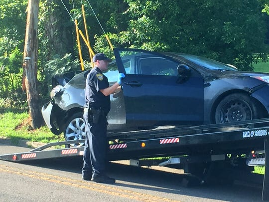 Tallahassee Police officers look through a car that was hit by a CSX train early Wednesday morning.