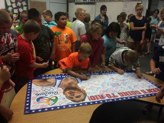 Students at Madison Elementary School sign a banner for Olympic athlete Ben Provisor.