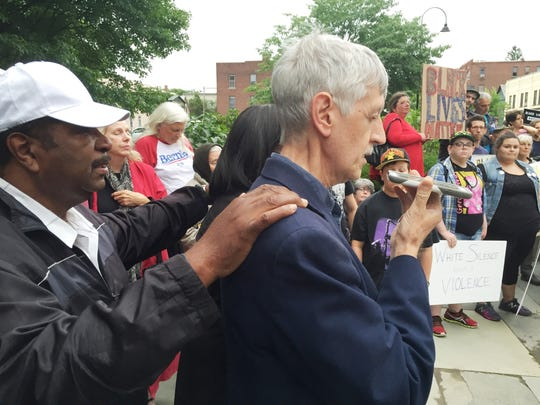 Pastor Mark Demers of Burlington's First United Methodist Church, at right, prays, backed by the Rev. Leroy Dixon of Missionary Baptist Church in Burlington.