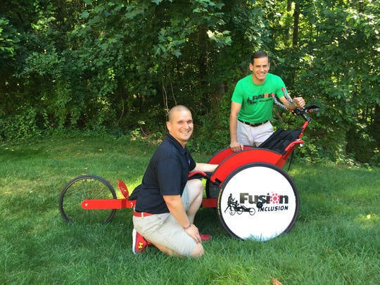 Nic DeCaire (left) and Steve Sinko pose with their Fusion Inclusion racing chair.