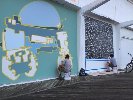 Bradley Hoffer (left) and James Vance paint their murals on Sunset Pavilion.